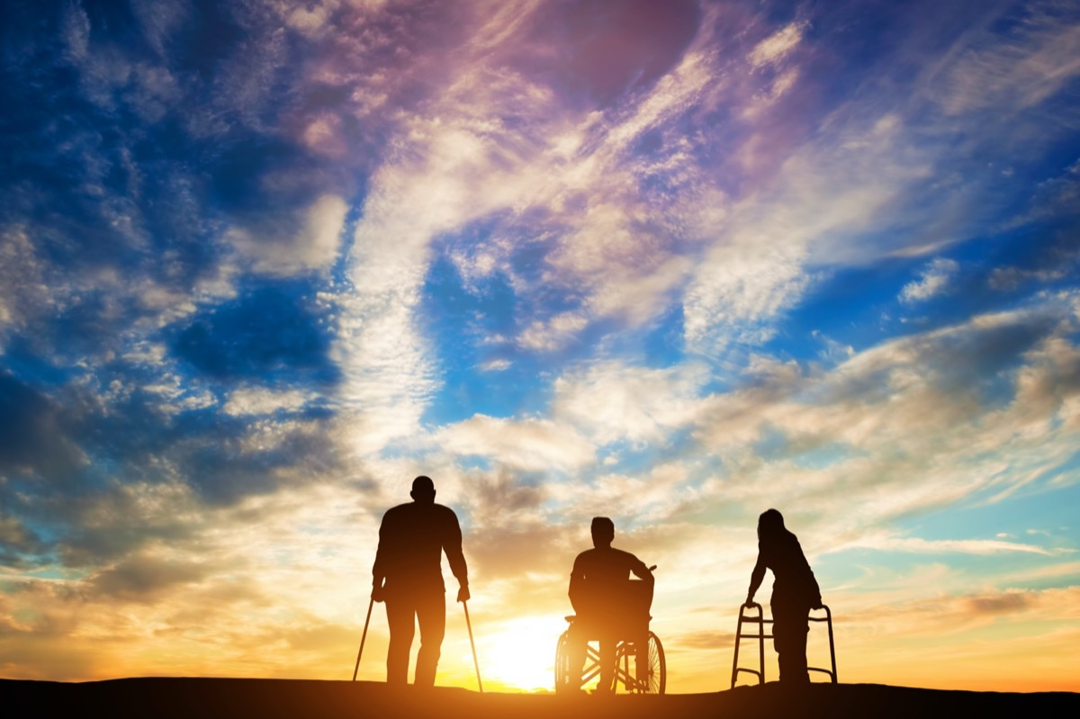 A person using crutches, a person in a wheelchair, and a person using a walker admire a beautiful sunset