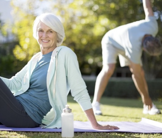 Senior woman sitting outdoors on yoga mat with water bottle, man in background doing stretching exercises